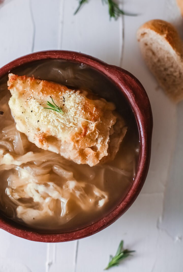 Onion soup in a bowl with crusty bread.