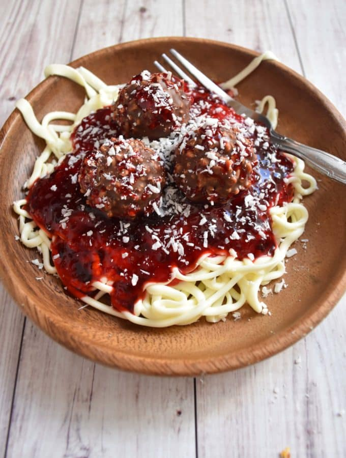 spaghetti and meatballs on a plate look just like the real thing but made with frosting, jam, and truffles. Great for April Fools Day!