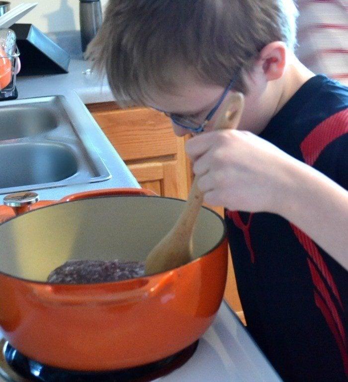 adorable boy making lasagna soup