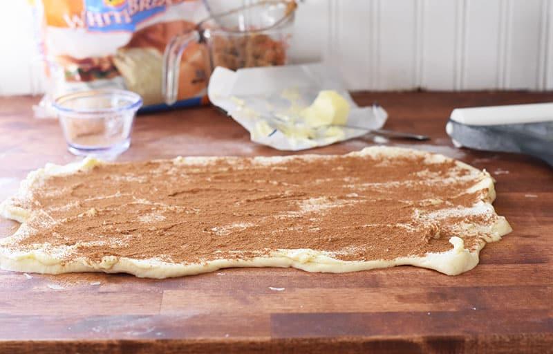 sprinkling cinnamon on frozen bread dough
