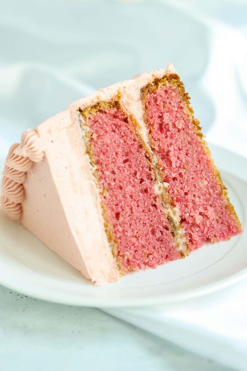 slice of homemade strawberry cake with strawberry frosting