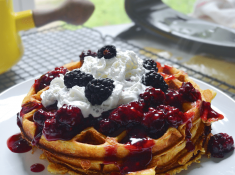 Cornbread waffles with blackberry whiskey sauce. breakfast