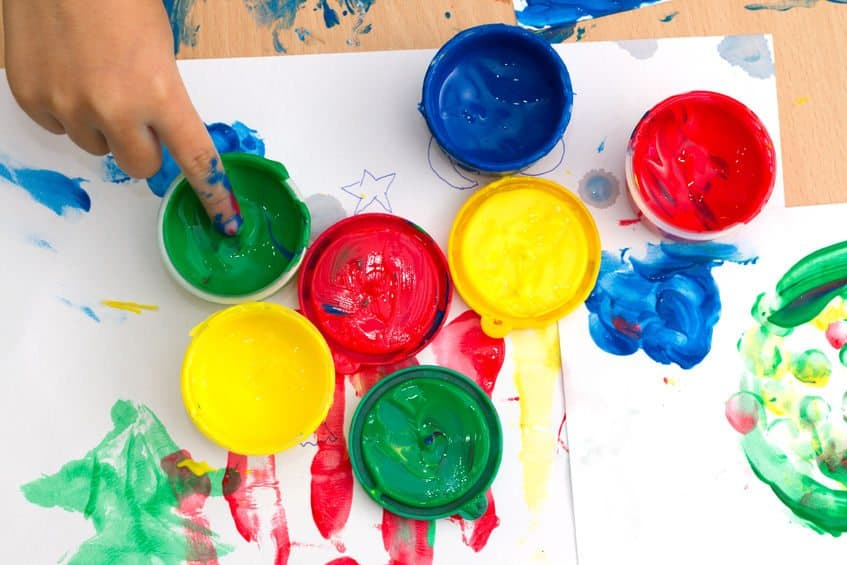 48541554 - colorful finger paints with childrent hand on a table