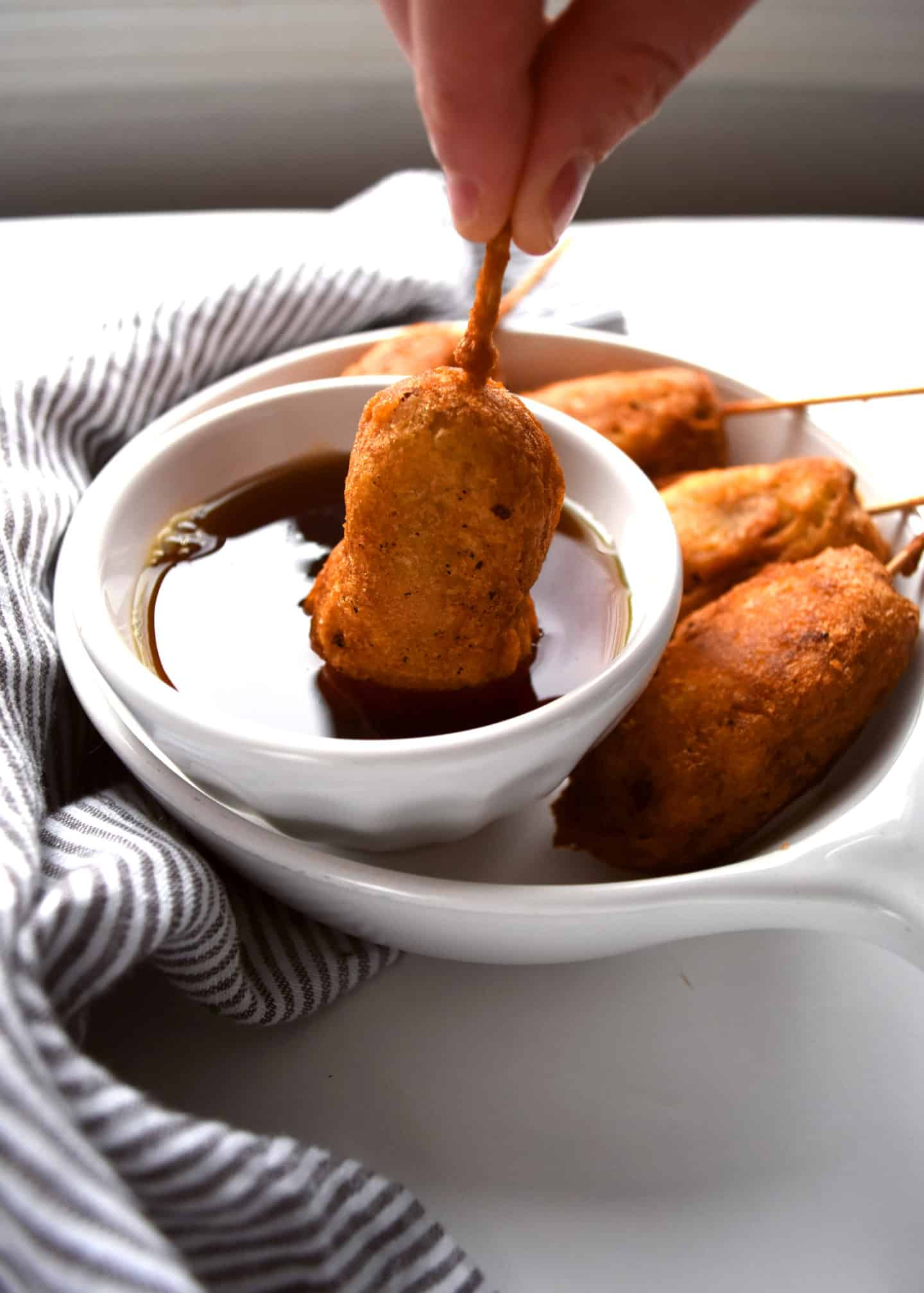 breakfast corn dogs being dipped into maple syrup