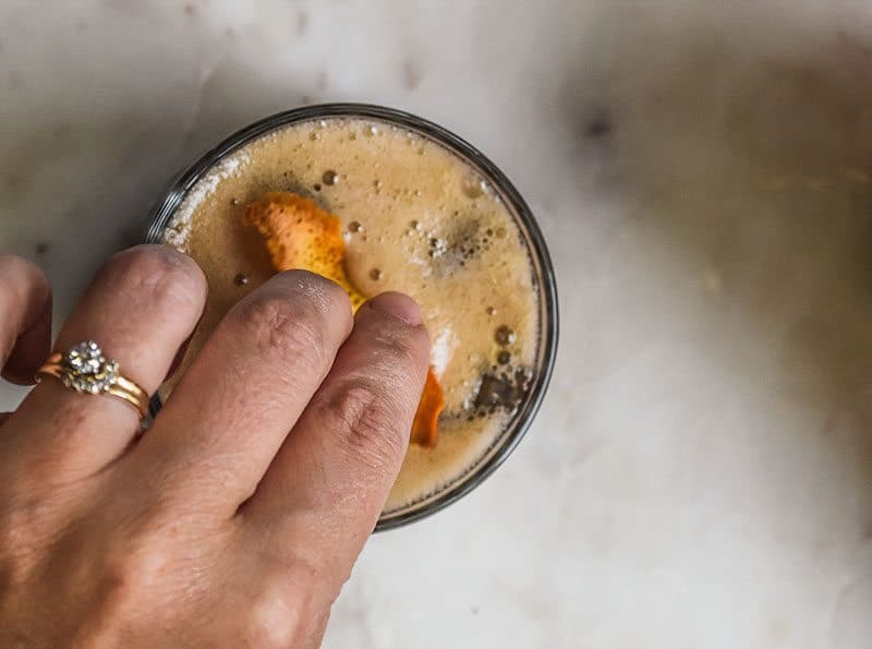 Add a bit of orange slice to the root beer cocktail.