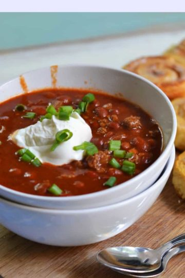 venison chili in a bowl topped with sour cream and green onions