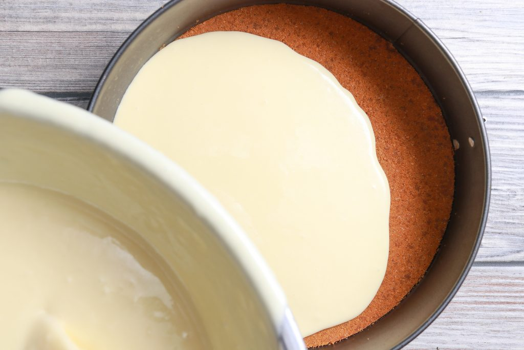 pouring the batter for the cheesecake into the pan