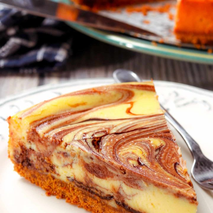 slice of hot fudge marble cheesecake on a plate with a pan of cheesecake in the background