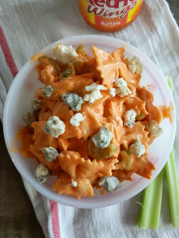 buffalo chicken salad in a bowl with blue cheese on top, celery sticks alongside, and a bottle of RedHot buffalo sauce