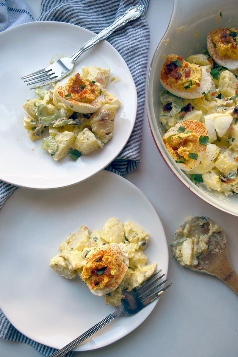 deviled egg potato salad on two plates with forks