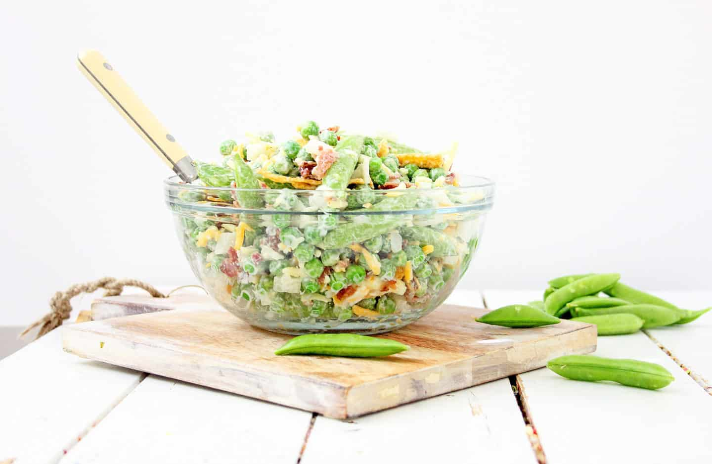 A bowl of pea salad with fresh peas, bacon, shredded cheese, and more.