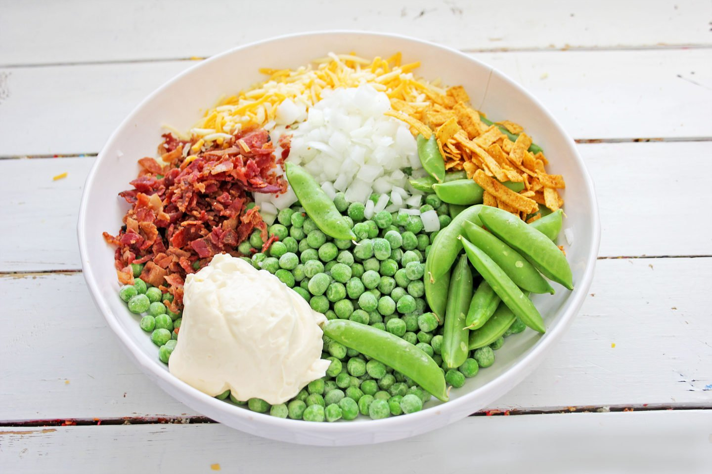 Ingredients for green pea salad recipe. Bacon, sweet peas, cheddar cheese, onion, sour cream.