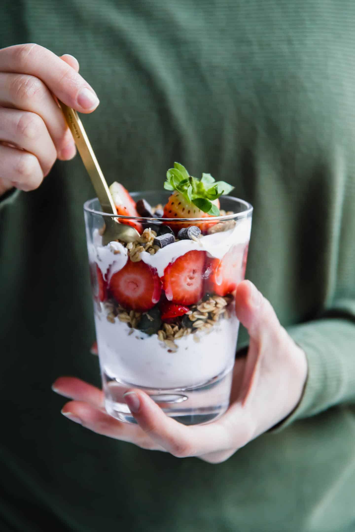 Breakfast parfait with layers of yogurt, granola, and strawberries