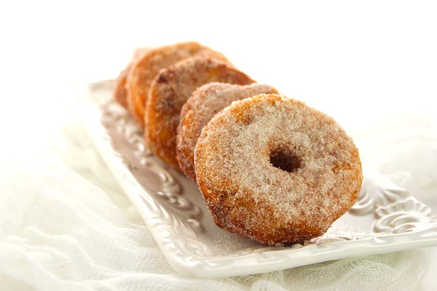 These homemade donuts are made with canned biscuits and covered in cinnamon and sugar.