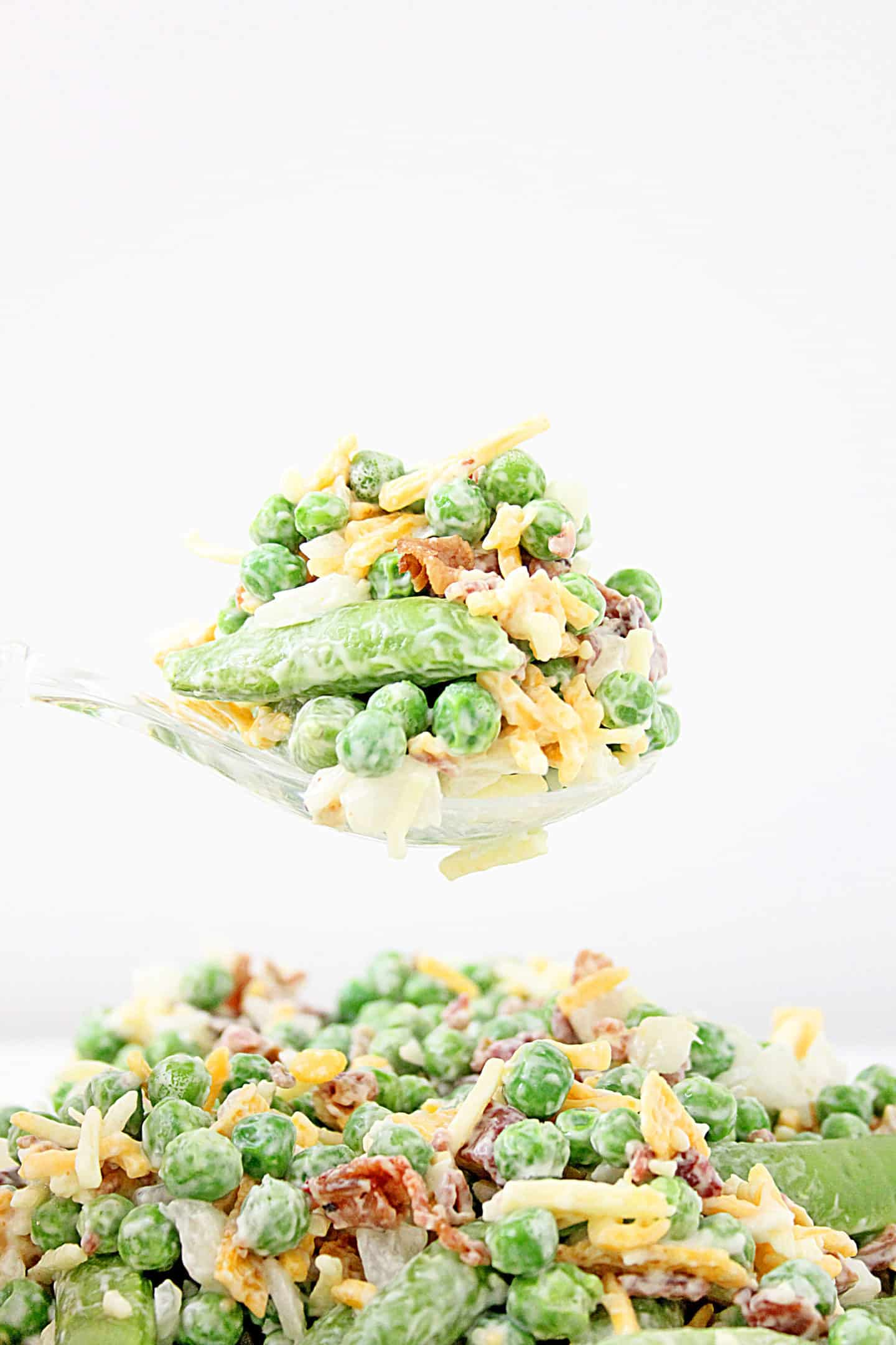 crunchy pea salad on a spoon with fresh peas, bacon, green beans, and shredded cheese.