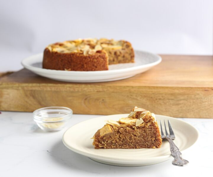A plate with a slice of almond cake with apples and almonds.