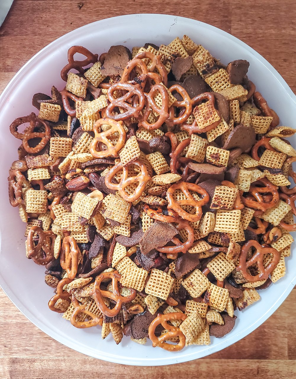 Homemade chex mix with Chex cereal, rye crackers, pretzels, mixed nuts, butter, and seasonings.