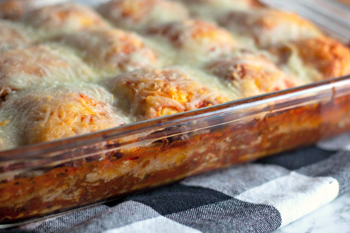 A pan with layers of hot sauce, cheese, and ravioli baked up.