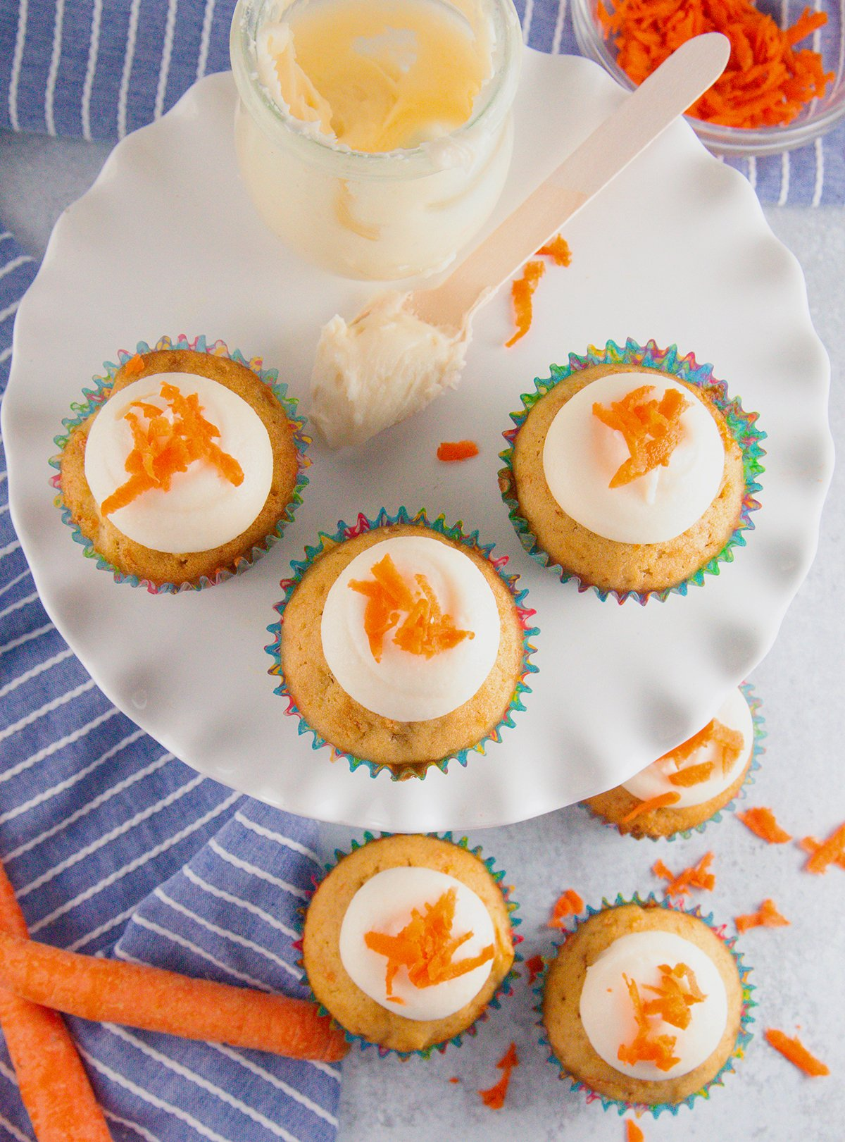 A yummy plate full of cream cheese frosting topped carrot cupcakes
