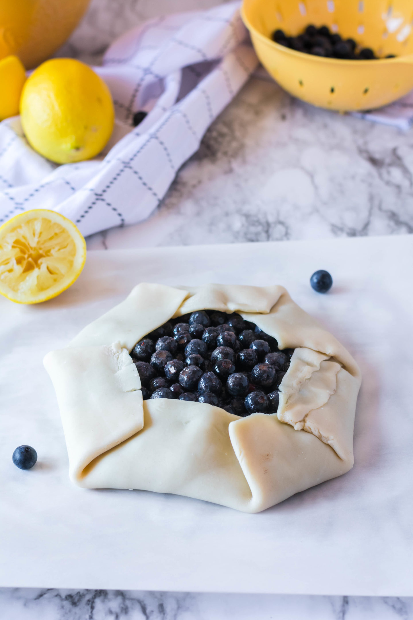 A rustic blueberry tart ready to be baked.