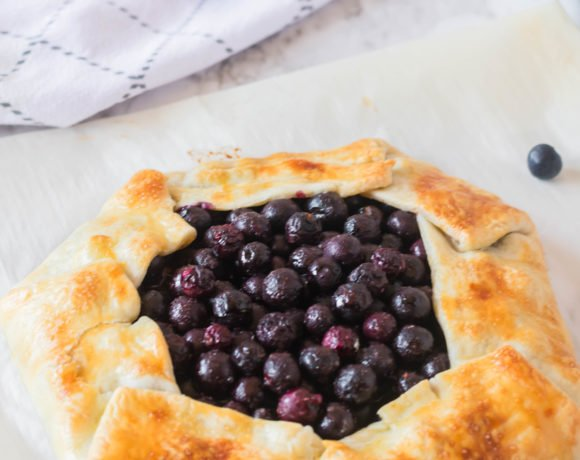 A rustic blueberry tart full of fresh berries wrapped in a pie crust.
