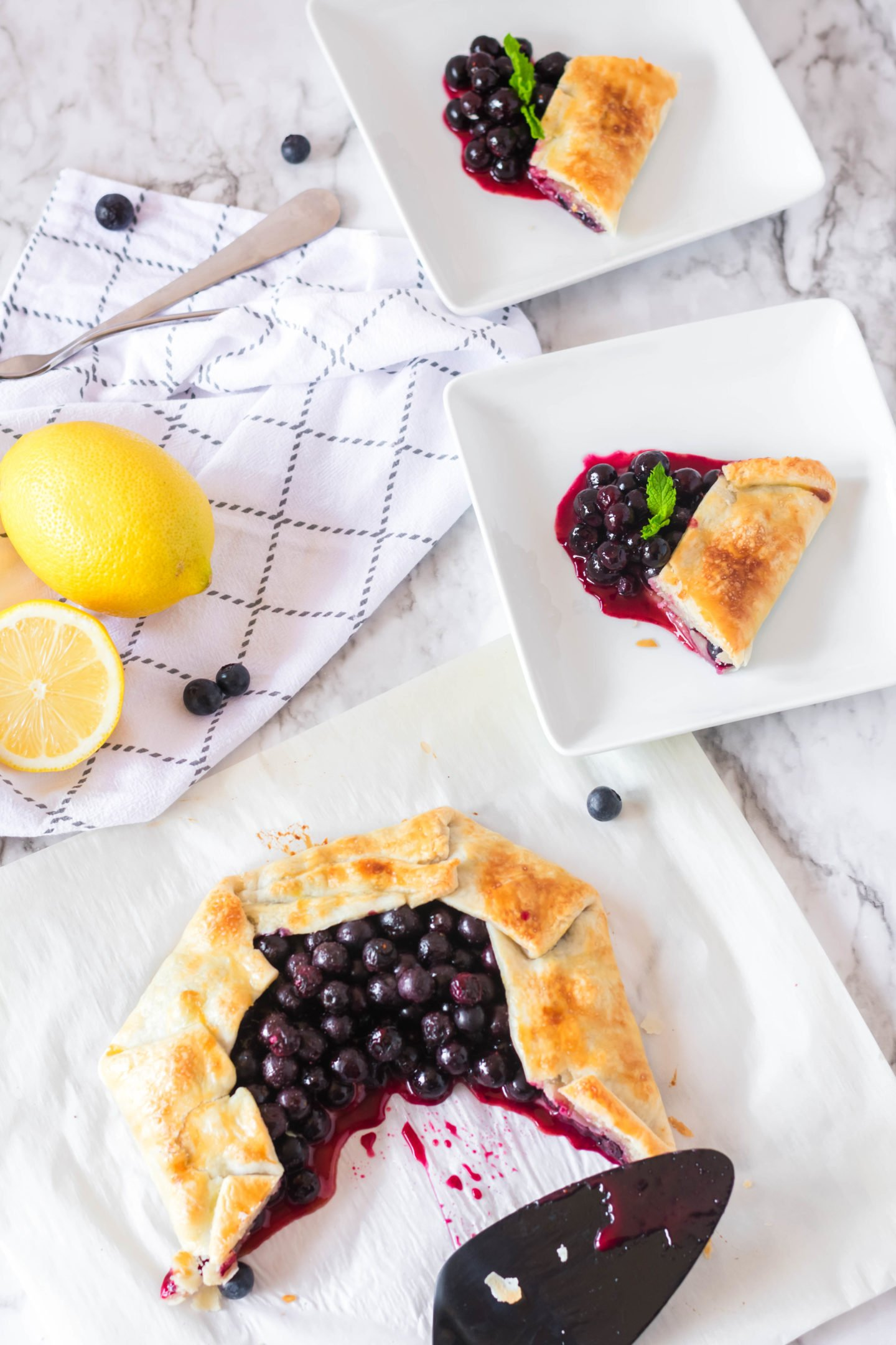 Rustic fresh blueberry tart served up on dishes for sharing.