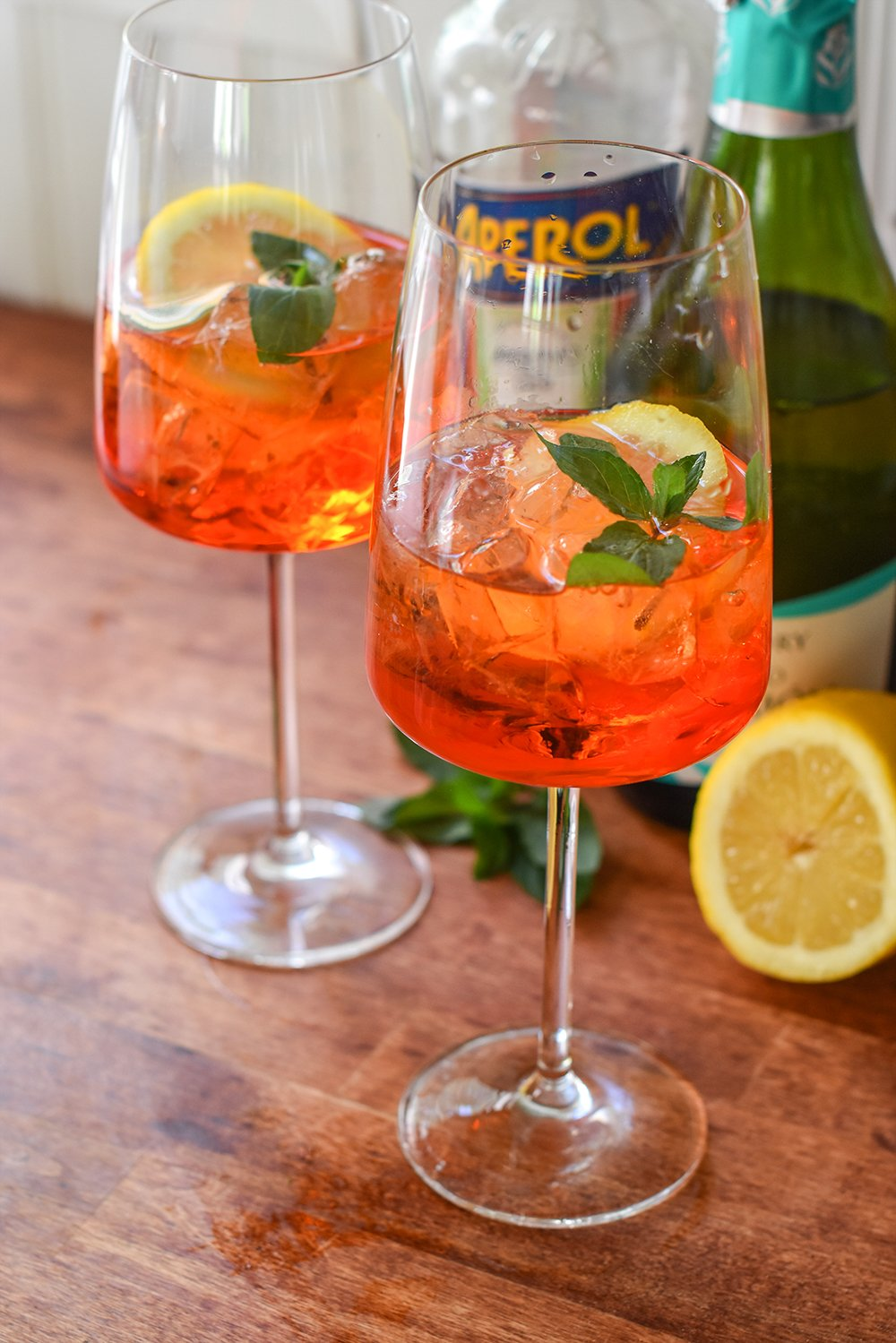 An easy Aperol wine spritzer garnished with fresh lemon and mint sprigs.