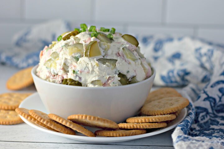 dill pickle dip with ham in a bowl with crackers