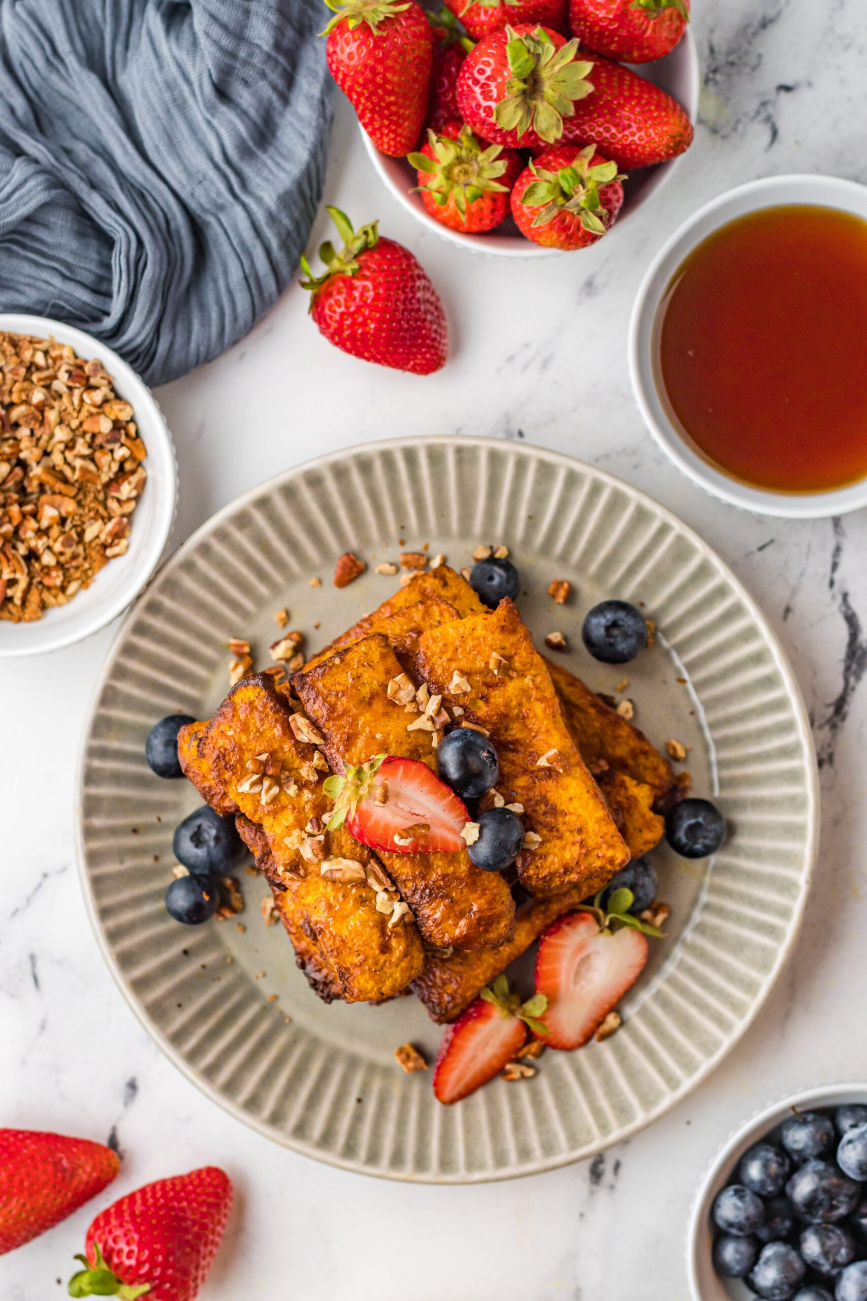 A plate of french toast sticks with fresh fruit.
