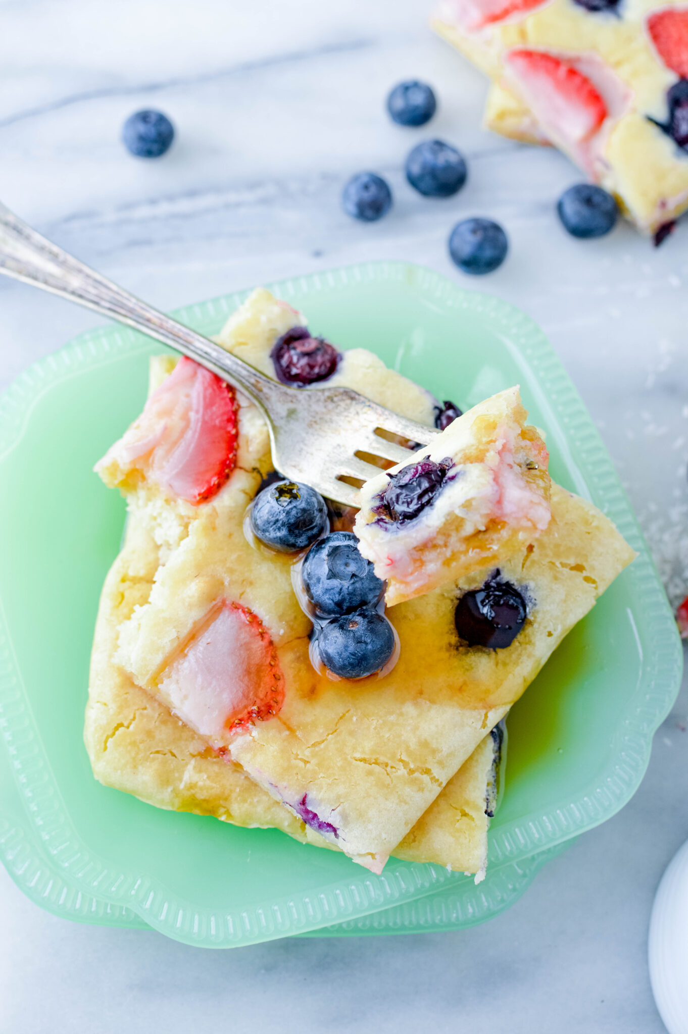 a plate of sheet pan pancakes with fruit and syrup on top.