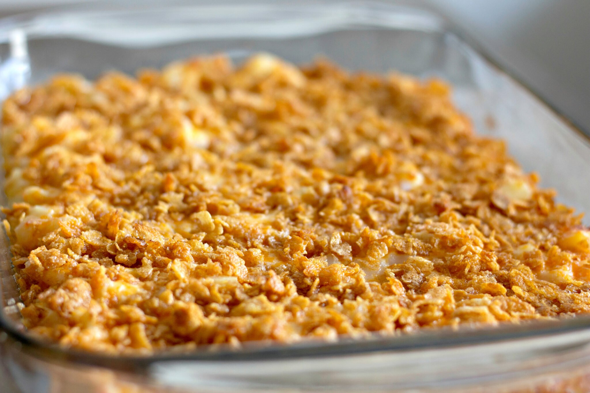A pan of cheesy potatoes topped with buttered, crushed cornflakes.