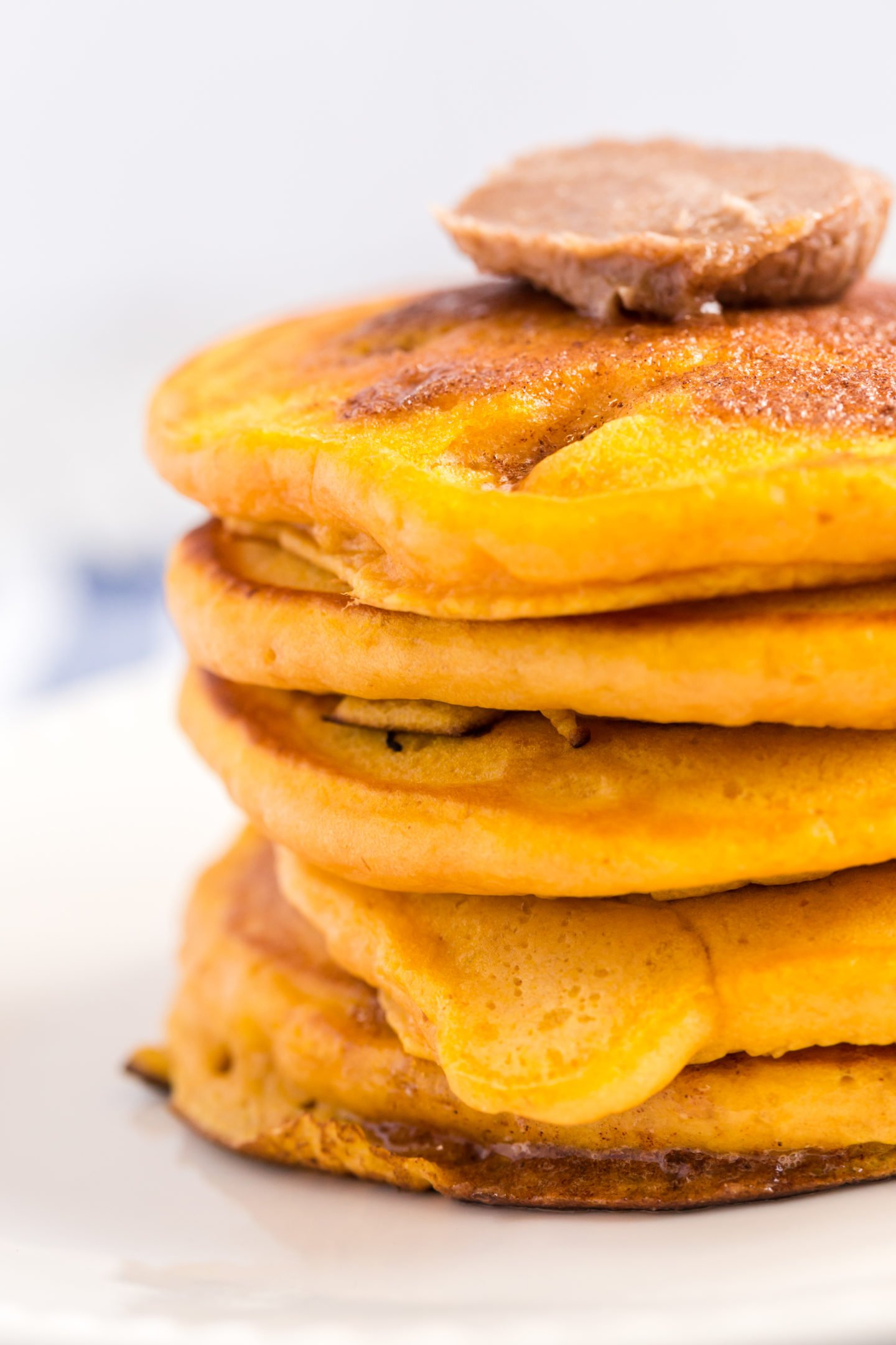 stack of fluffy and hearty pumpkin pancakes topped with cinnamon butter