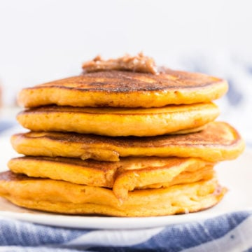 A stack of pumpkin pancakes with a dollup of cinnamon butter on the top.
