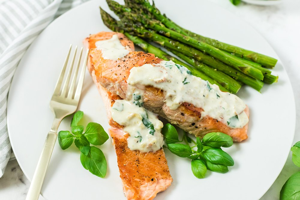 Pan roasted salmon on a plate with creamy garlic sauce