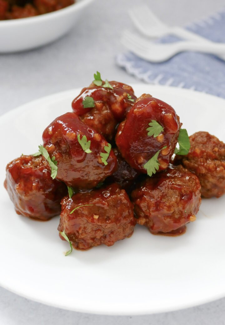 Sweet & spicy crockpot meatballs on a plate topped with green onions.
