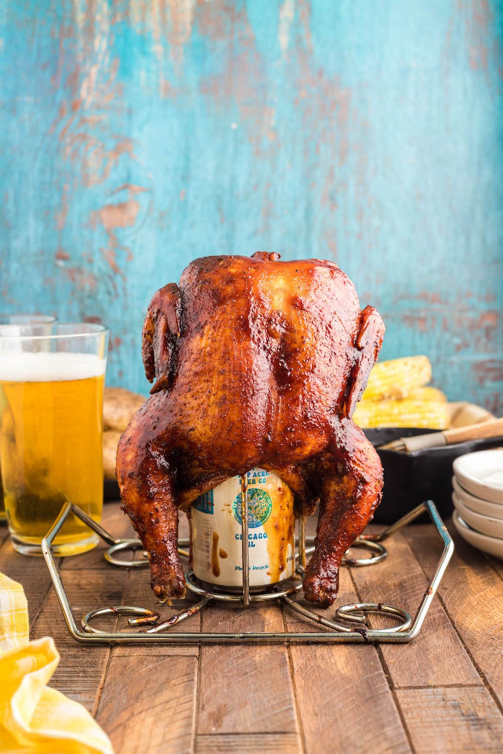 Whole Beer Can Chicken with plates, corn, and beer