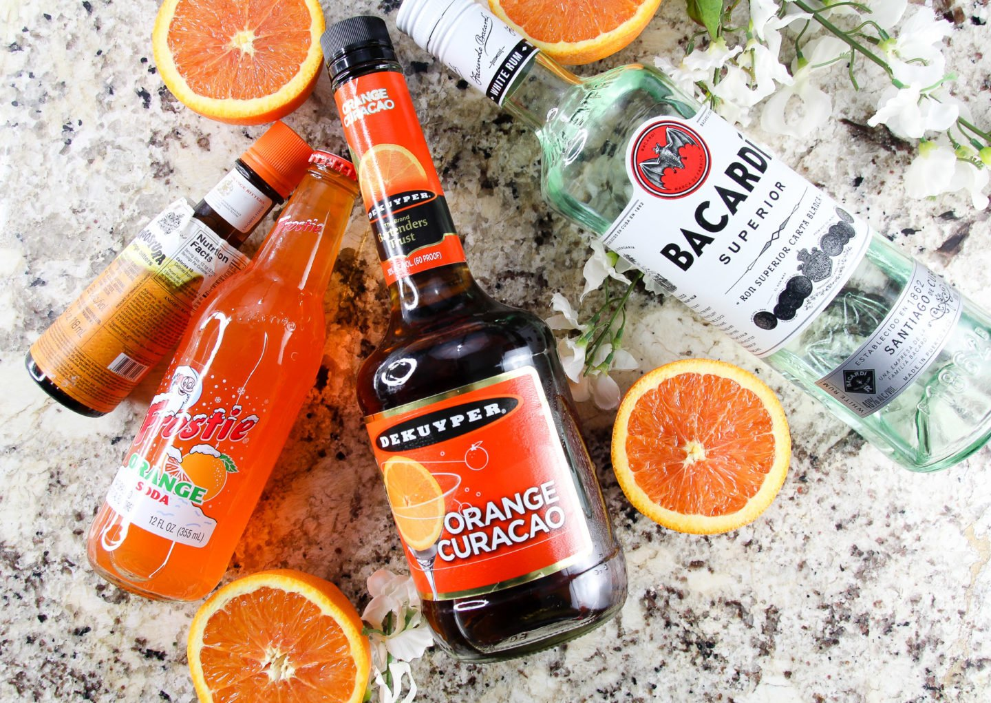 Ingredients needed for orange sunset cocktail are orange soda, orange curacao (or triple sec), and rum.