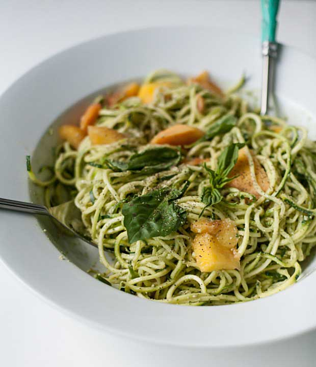 Bowl of zucchini noodles with pumpkin seed pesto and peaches