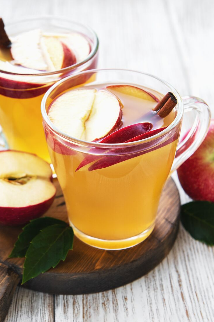 Apples, cinnamon, and whiskey in a clear mug filled with a hot toddy.