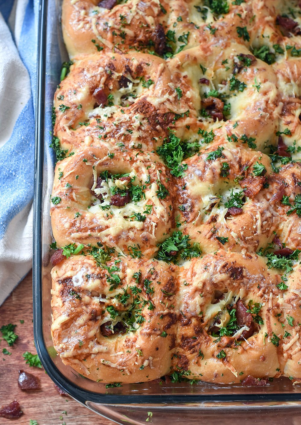Baked dinner rolls with cheese, bacon, and fresh parsley on top.