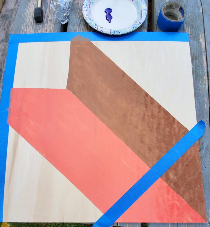 Taping up the diy barn quilt board for the center square