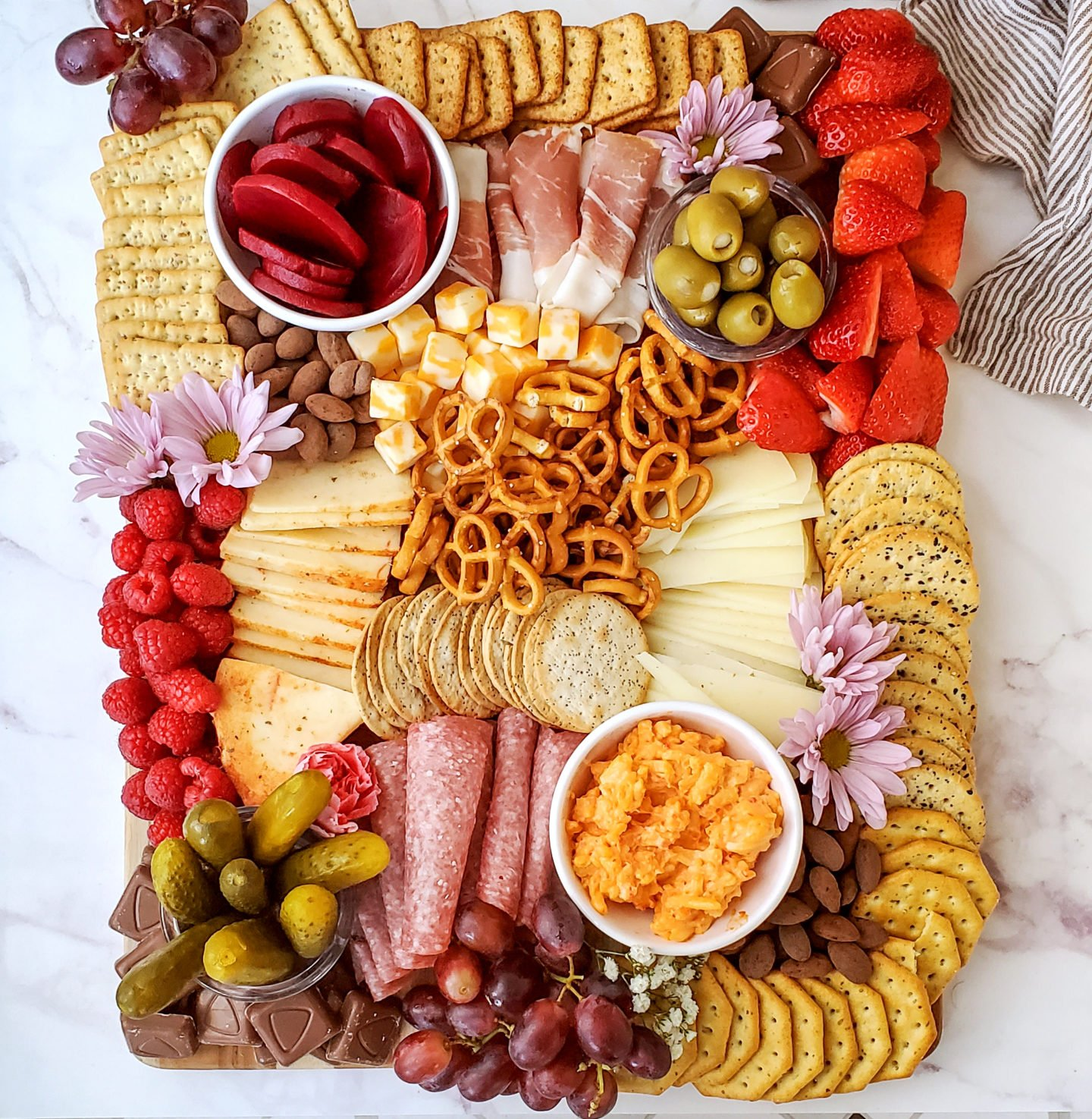 Charcuterie board full of meats, cheeses, veggies, crackers, and more
