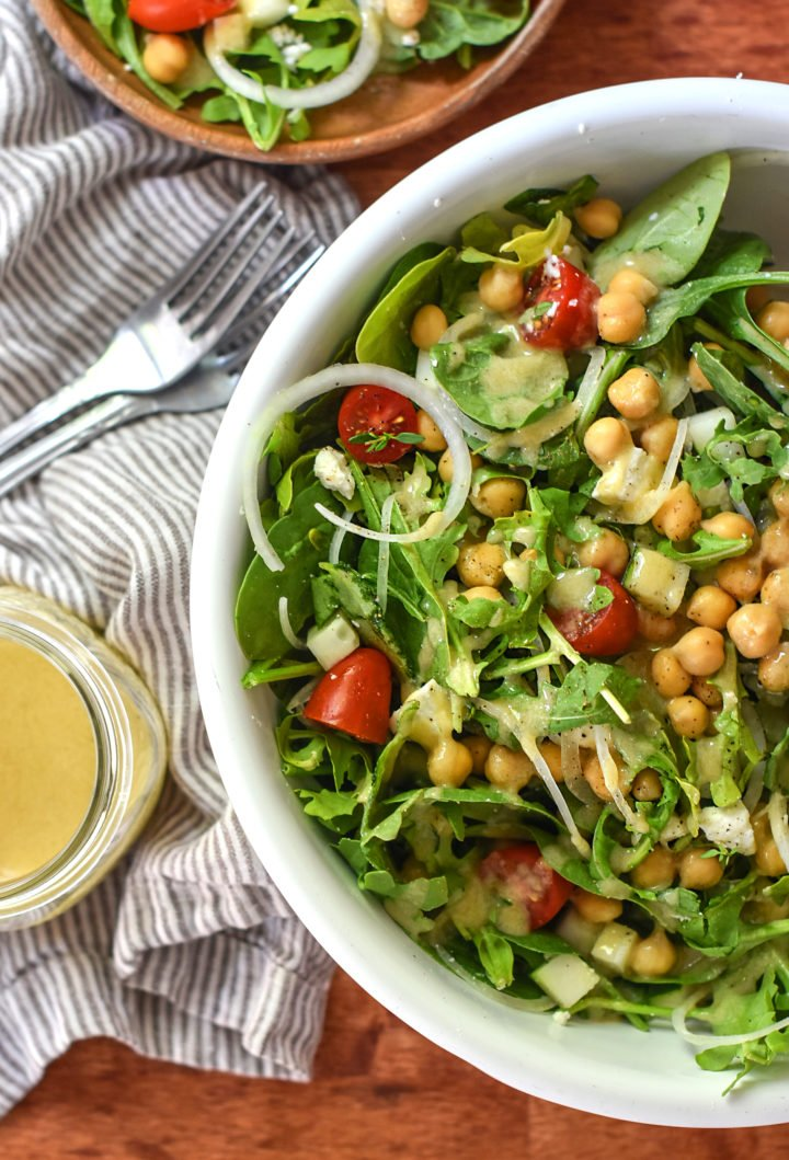 A bowl of arugula mixed with chickpea and fresh veggies for the ultimate summer salad!