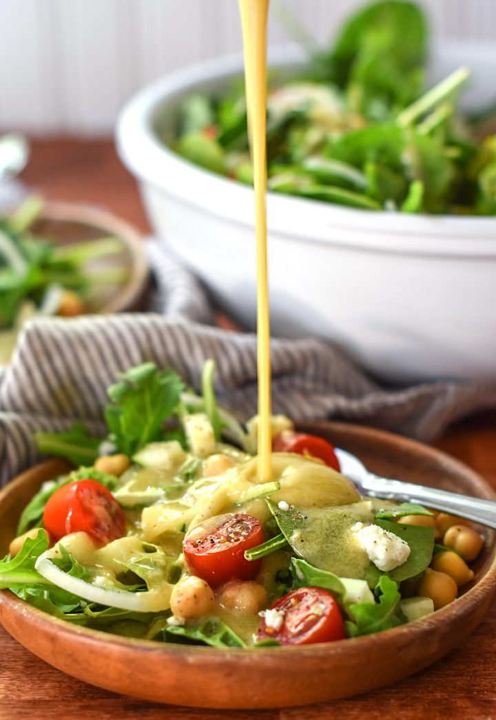 Creamy tahini dressing poured over a beautiful chickpea and arugula salad