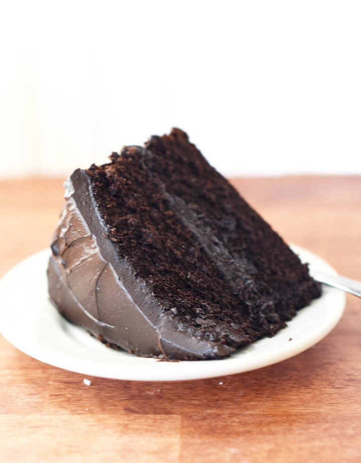 A slice of homemade chocolate cake with chocolate frosting on a plate