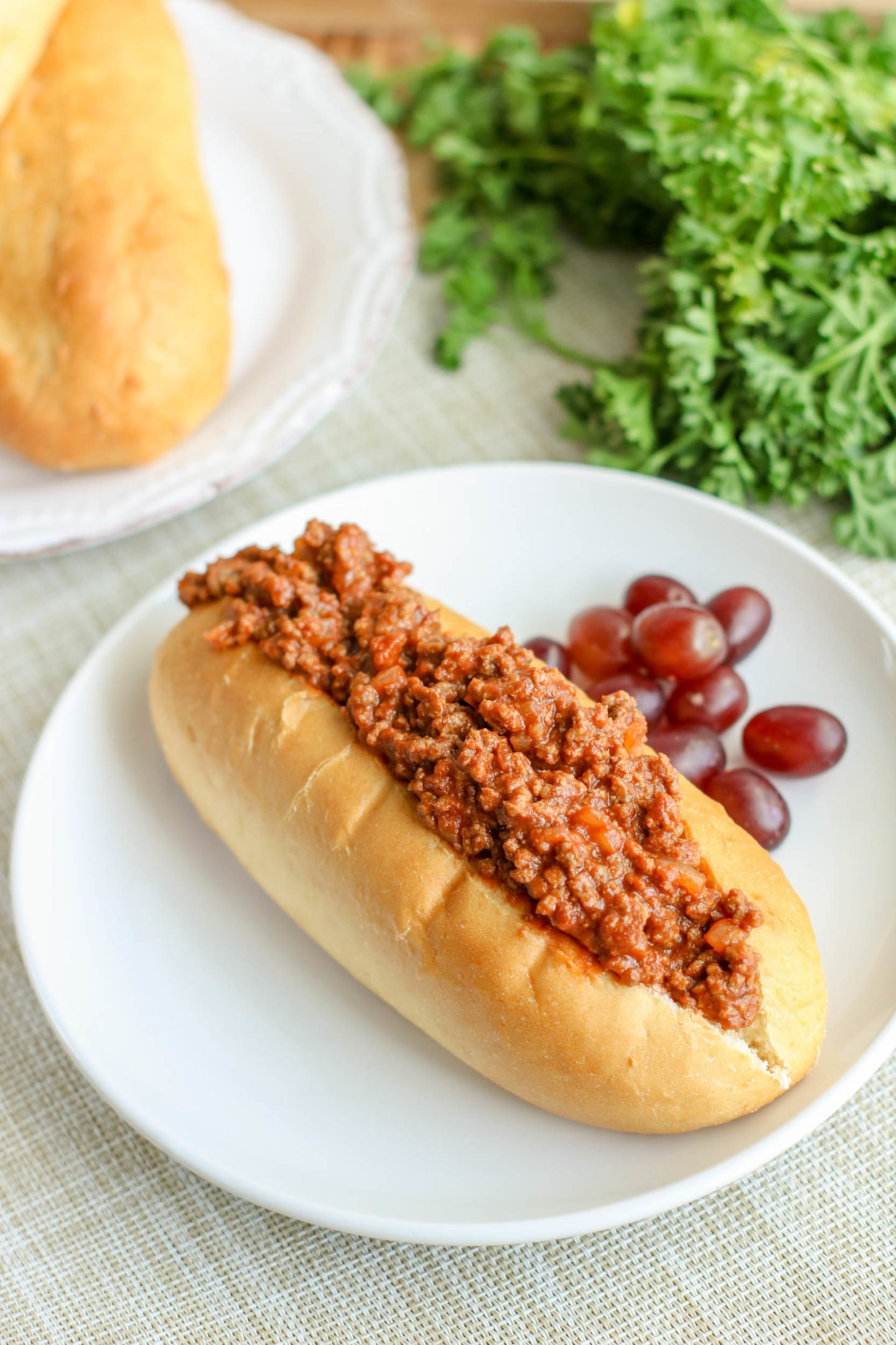 The finished sloppy joes in a bun, on a plate.
