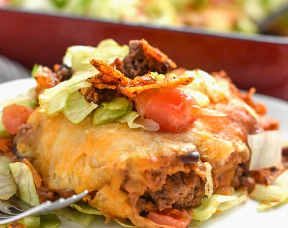 Dorito pie or casserole on a plate with a pan in the background. An easy family friendly meal!