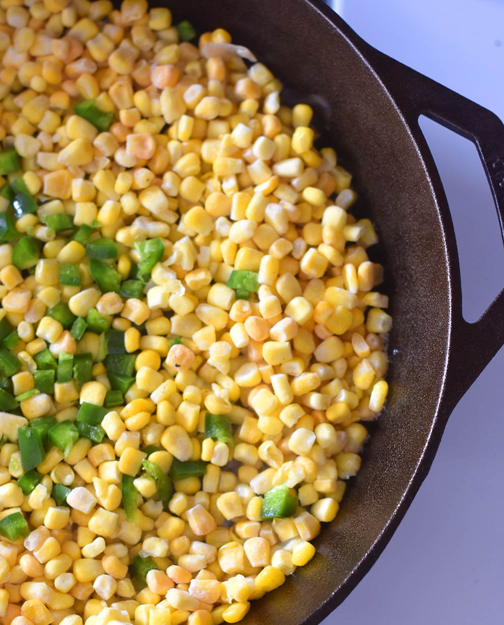 Frozen sweet corn and diced jalapeno in a cast iron pan getting ready to be made into Mexican Street Corn Dip.