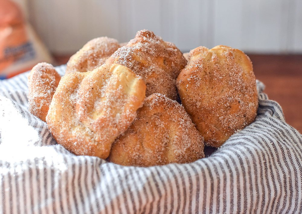 a bowl of bread dough fried in the air fryer and dipped in cinnamon and sugar.