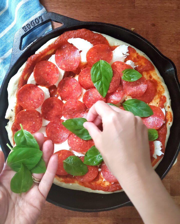 deep dish pizza in a cast iron pan being topped with fresh basil